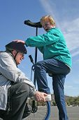 stock photo of unicycle  - Senior Man Giving Boost to Senior Woman for Unicycle Ride - JPG