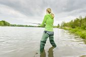stock photo of fisherwomen  - woman fishing in pond in spring country - JPG