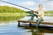 stock photo of fisherwomen  - fishing woman sitting on pier in summer country - JPG