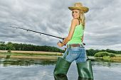stock photo of fisherwomen  - woman fishing in pond in green spring country - JPG