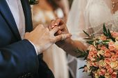Beautiful Bride And Groom Hands Exchanging Wedding Rings In Church During Wedding Ceremony. Spiritua poster