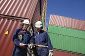 two workers inside busy container-port, stacks of cargo-containers in background