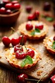 Mini Tarts With Fresh Cherries And Vanilla Custard And Caramel, Delicious Dessert On A Wooden Table, poster