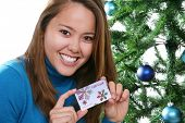 A pretty girl at Christmas holding a gift card