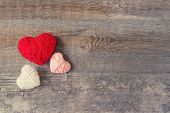 Three Red, White, Pink Thread Heart On Dark Wooden Vintage Background. Handmade Pretty Heart. Love,  poster