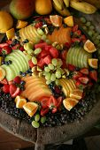 stock photo of fruit platter  - Assorted tropical fruit melon grapes and berries - JPG