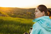 Young Female Traveller Is Drinking A Coffee From The Travel Metallic Cup On The Sunset. Concept Of T poster