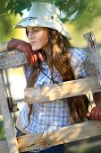 Portrait of beautiful cowgirl in stetson next to wooden fence