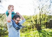 A Father With His Toddler Son Outside In Green Sunny Spring Nature, Having Fun. Copy Space. poster