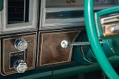 Dashboard And Steering Column Of An Old Vehicle With Wood Veneer Finish And Green Steering Wheel poster