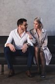 Sexy Young Woman In Coat And Stockings Flirting With Handsome Young Businessman Sitting On Sofa poster