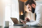 Young Bearded Businessman In Shirt Sitting At Desk In Front Of Laptop, Making Notes In Digital Table poster