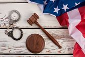 Handcuffs, Wooden Gavel And Usa Flag. Unites States Flag, Metal Handcuffs And Judge Gavel, Top View. poster