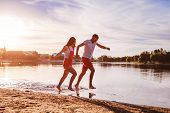 Young Man And Woman Running On Summer River Bank. Couple In Love Having Fun At Sunset. Guys Chilling poster