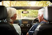 Senior Couple Drive Open Top Car On Countryside Road Trip poster