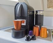 Closeup Still Life Of Espresso Coffee Maker Machine With Mug Cups And Capsule Pods poster