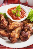Spicy grilled chicken wings with chili sauce poster