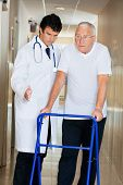 Doctor helping senior patient walk down hallway using Zimmer frame