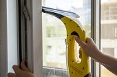 Wash The Window At Home With A Battery Wiper. The Apparatus Yellow Collects Drops Of Water And Clean poster