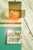 Conceptual Hand Writing Showing Developing Strategy. Business Photo Text Game Plan That Sets Specifi poster