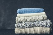 Pile Of Knitted Woolen Sweaters. Clothes With Different Knitting Patterns Folded In Stack. Warm Cozy poster