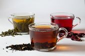Black Hot Tea With Dry Leaves.three Glass Cups With Black, Red And Green Tea With Dry Leaves On A Wh poster