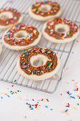 Homemade Sugar Cookie Buttercream Icing Donuts With Sprinkles On Cooling Rack. poster