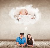 Young Couple Lying On The Floor And Imagine Their Future Baby. Over Beige Wall Background poster