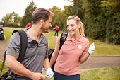 Mature Couple Playing Round Of Golf Carrying Golf Bags And Talking poster