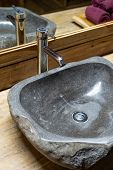 Vertical And Close Up View Of Bathroom With Stone Sink Basin, Faucet And Mirror On Wooden Table poster