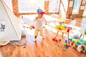 Beautiful blonde toddler wearing fanny colorful propeller cap. Standing around lots of toys at kinde poster