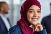 Portrait of young muslim woman wearing hijab in office while looking at camera. Close up face of ara poster