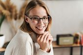 Photo of smiling attractive woman in eyeglasses looking at camera while sitting in cozy living room poster