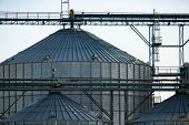 Closeup View Of A Large Scale Agrarian Facility, Large Steel Silos Are Seen With Pipes, Access Ladde poster