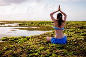Young Woman, Meditating, Practicing Yoga And Pranayama At The Beach. Sunrise Yoga Practice. Hands Ra poster