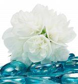 Delicadas flores de jasmim brancas em pedras de vidro azul