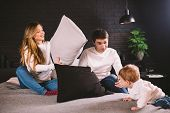 Family Having Funny Pillow Fight On Bed. Parents Spending Free Time With Their Son. Young Family Bei poster