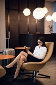 Businesswoman Sitting At The Airport Bussiness Lounge, Waiting For The Flight. Smiling Woman Wearing poster