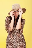 Seductive elegant woman peering out from under her wide brimmed straw sun hat