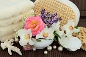 Rose, elderflower, syringa and lavender herb flower blossom, with bath accessories over bamboo.