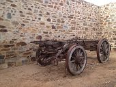 old wooden wagon near stone wall