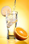 Pouring Of Mineral Water In Glass With A Lemon And Orange On A Yellow Background