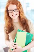 Teenage girl in eyeglasses holding books and looking at camera with smile