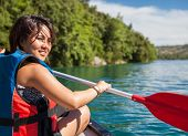 Pretty, young woman on a canoe on a lake, paddling, enjoying a lovely summer day