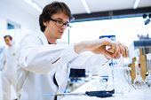 Young male researcher carrying out scientific research in a lab (shallow DOF; color toned image)