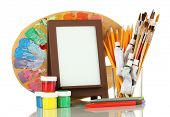 Photo frame as easel with artist's tools isolated on white