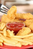 Fried chicken nuggets with french fries and sauce on table in cafe