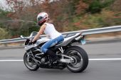 stock photo of crotch-rocket  - A pretty blonde girl in action driving a motorcycle at highway speeds - JPG