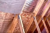 Gable View Of Ongoing House Attic Insulation Project With Heat And Cold Barriers