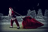 Santa Claus pulls a huge bag of gifts
